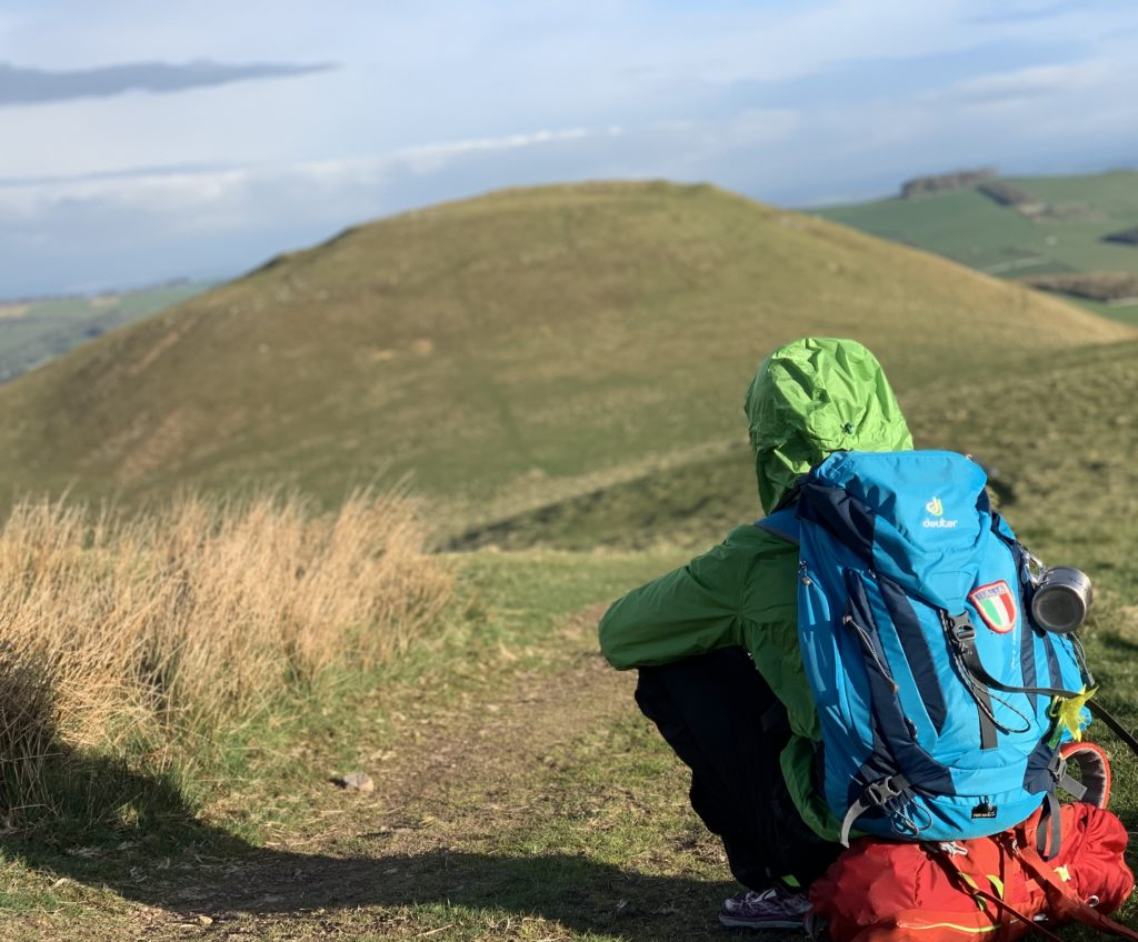 Skyrunning Girl - Sitting down in a field in Scotland